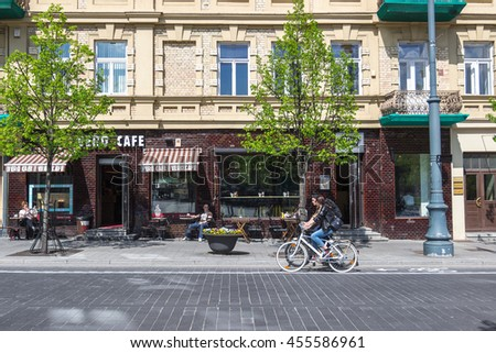 VILNIUS, LITHUANIA - MAY 5, 2015. Green spring street of Vilnius (Gedimino avenue) with young trees and people sitting at cafe, woman riding bike in sunny day.