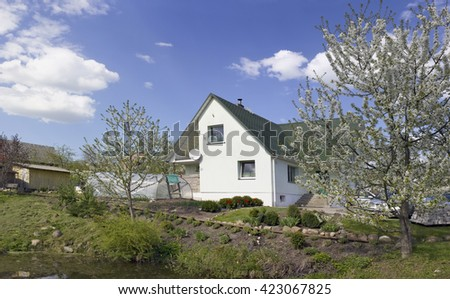 VILNIUS, LITHUANIA - MAY 07, 2016: Spring in garden association Kalorija on lake bank near the village - Rastenenai. Blossom apple trees. Handmade white home with green roof and red tulips landscape