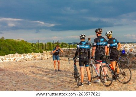 Vilnius, Lithuania - May 1, 2014: Young athletes cyclists in vivid sports uniform and helmets with bicycles are photographed on Castle Hill in Vilnius
