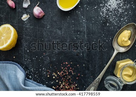 Vinaigrette dressing - recipe ingredients on black chalkboard background from above (flat lay). Lemon, olive oil, mustard, garlic, salt and pepper. Layout with free text space. - stock photo