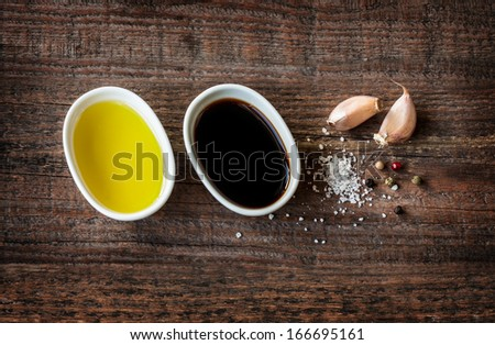 Vinaigrette or french dressing recipe ingredients on vintage wood background. Olive oil, balsamic vinegar, garlic, salt and pepper from above. - stock photo