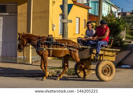 VINALES - FEBRUARY 4: Two young men on a cart on February 4, 2013 in Vinales, Cuba. Carts are very common type of transportation in Cuba as not everyone can afford to buy a car.