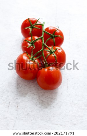 vine tomatoes are placed against a white wooden background - stock photo