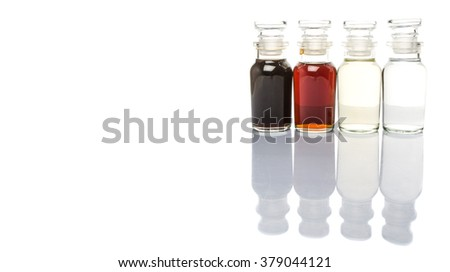 Vinegar, balsamic vinegar, maple vinegar and apple vinegar in glass vial over white background