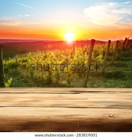 vineyard at sunset in the Chianti region in Italy and wooden desk of free space for you and garden  - stock photo