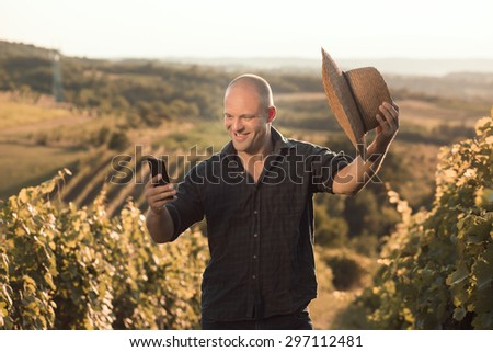 Vineyard owner taking selfie with smart phone - stock photo