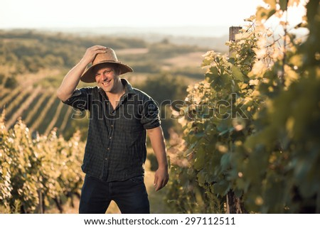 Vineyard owner with hat standing in his vineyard - stock photo