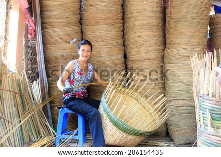 Vinh Long city, Vietnam - 06 May 02, 2015: Unknown, An Asian woman weaving handicraft basket from bamboo. The fruit trader on floating market in the Mekong Delta will need the baskets like these