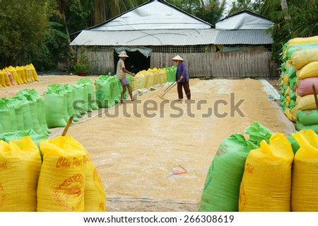 VINH LONG, VIET NAM- MAR 23: Couple of Asia farmer dry rice on drying ground, group of paddy bag to temporary storage when crop finish, Mekong Delta is big Vietnamese granary, Vietnam, Mar 23, 2015