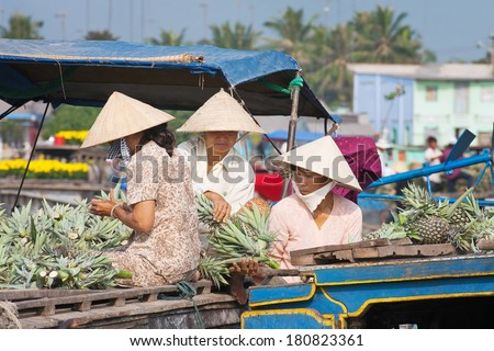 VINH LONG, VIETNAM - FEBRUARY 3, 2005 : Three women wearing conical hats sit on a boat preparing pineapples for sale at the Cai Be floating market near Vinh Long, Vietnam.