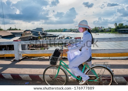 VINH LONG, VIETNAM - MARCH 7: School girl in white school dress bikes home on March 7, 2009 in Vinh Long. Education in Vietnam is divided into five levels from preschool to higher education.