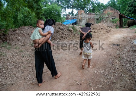 Vinh Phuc, Vietnam, May 12, 2016 a grandmother, carried him on his back, on his way home, rural Vinh Phuc, Vietnam