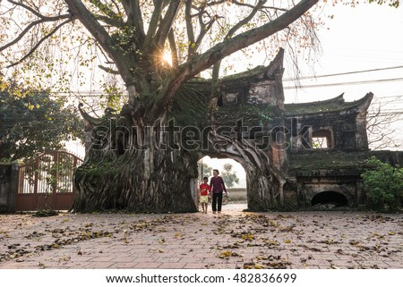 VINHPHUC, VIETNAM, APRIL 10, 2016: A boy with his grandmother go through an ancient gate in a village in Vinh Phuc province, Vietnam. Village gate is a specific of Northern country side in Vietnam.