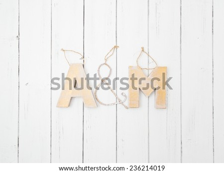 Vintage A&M letters made by hands of cardboard and metal wire. Christmas tree toys or wedding decorations decorated on a white wooden background - stock photo
