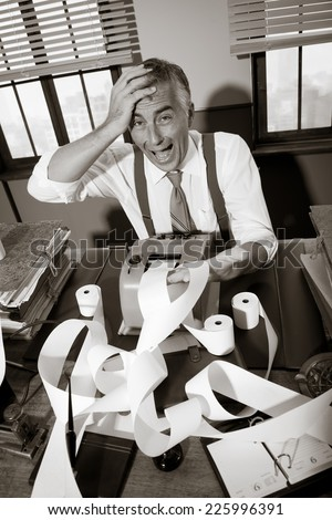 Vintage accountant checking errors on long bills on cash register tape with calculator. - stock photo