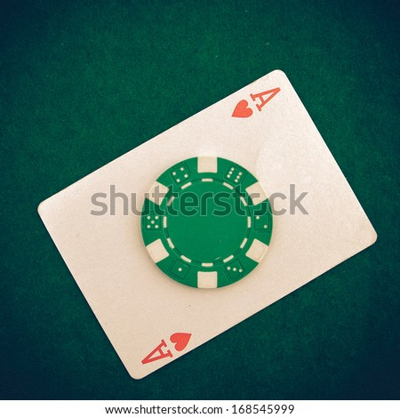 Vintage - Ace with casino chip on a green casino table with space for text - stock photo