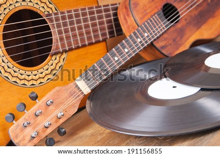 Vintage acoustic guitars and vinyl records on a wooden background