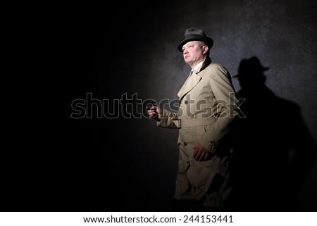 Vintage agent pointing a gun in the dark, film noir scene 1950s style - stock photo
