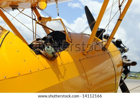 Vintage airplane detail showing cockpit and pilot gear - stock photo