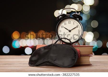 Vintage alarm clock and a sleep mask - stock photo