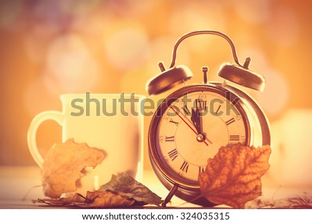 Vintage alarm clock and cup on yellow background with bokeh - stock photo
