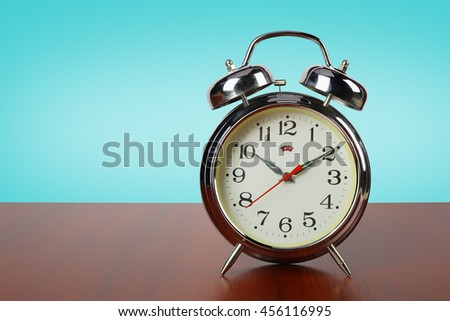 Vintage Alarm Clock - Old retro alarm clock on a wooden table and a blue background.