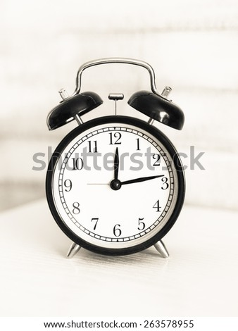 Vintage alarm clock on a table. Retro filter and mochromatic colors style. - stock photo