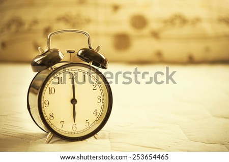 Vintage alarm clock on bed. - stock photo