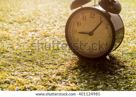 Vintage alarm clock on glass at morning - stock photo