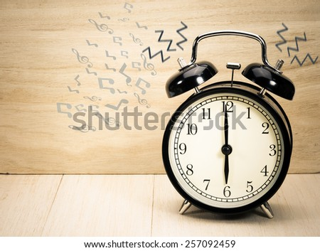 Vintage alarm clock on old wood wall table. - stock photo