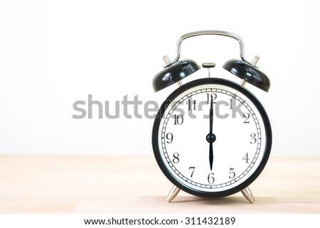Vintage alarm clock on old wood wall table. / Alarm clock show 6 o`clock on old wood table. - stock photo