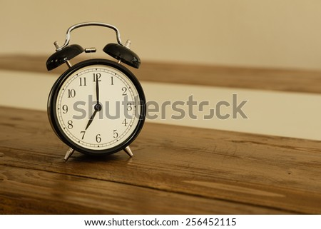 Vintage alarm clock on rustic wood table. Shows 7 o'clock.