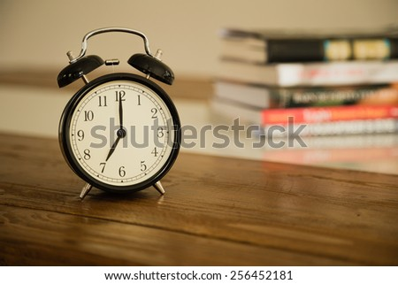 Vintage alarm clock on rustic wood table. Shows 7 o'clock. Pile of books in background.