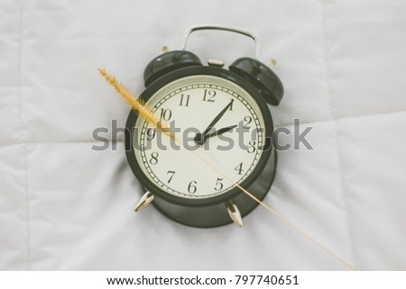 Vintage alarm clock on white bed in bedroom,wake up to work.