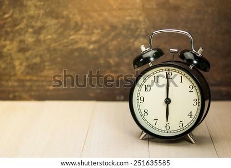 Vintage alarm clock on wood table. - stock photo