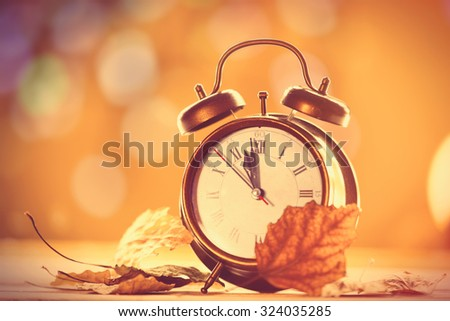 Vintage alarm clock on yellow background with bokeh - stock photo