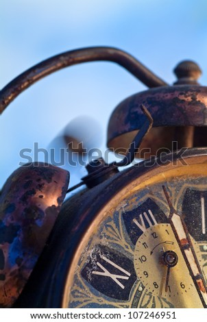Vintage alarm clock ringing on a blue background - stock photo