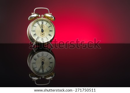 Vintage alarm clock showing five minutes to twelve, red background, copy space - stock photo