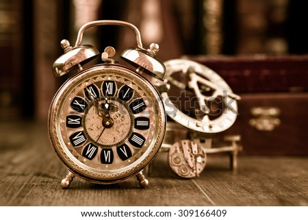 Vintage alarm clock showing five to twelve on the wooden table in study room. Happy New Year 2016! - stock photo