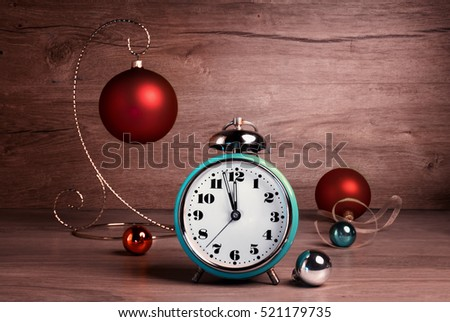 Vintage alarm clock showing five to twelve with Christmas baubles on wood. Happy New Year 2017!