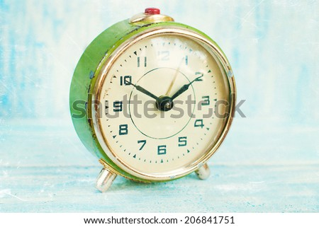 Vintage alarm clock. Time concept. Old color film effects with grain. - stock photo