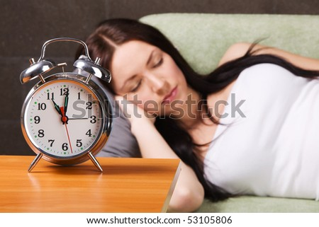 Vintage alarm clock, with beautiful young woman sleeping in the background - stock photo