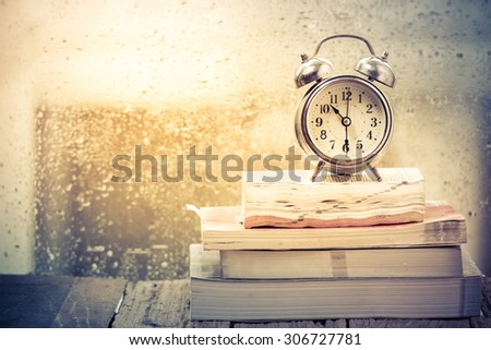 Vintage Alarm clock with book on a rainy day - stock photo