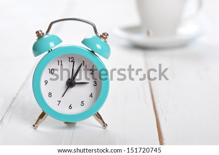 Vintage alarm clock with cup of coffee on white background  - stock photo