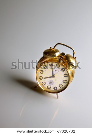 vintage alarm clock with reflection on gray background