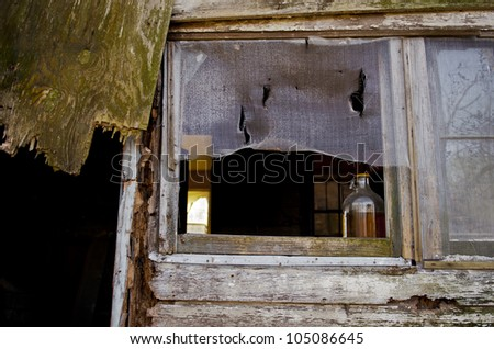 Vintage alcohol bottle in the window of a decaying building. - stock photo