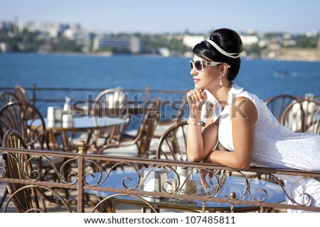 vintage alluring brunette woman relaxing in luxury hotel restaurant cote d'azure. Stylish rich slim girl in retro dress at villa apartment near sea.glamorous lady in sunglasses.vacation. Rero style - stock photo