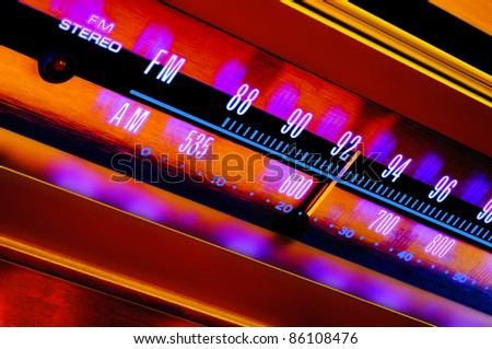 Vintage analog radio tuner dial FM/AM closeup with colorful psychedelic lighting - stock photo