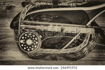 Vintage and aging grain concept of an antique fly fishing reel, rod, flies, and net on top of open creel with rustic wood underneath. Layout in horizontal format. - stock photo