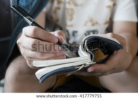 vintage and dark photo of Handwriting, hand writes a pen in a notebook. - stock photo